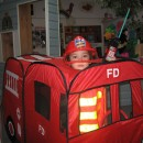 Child in fireman costume and play truck