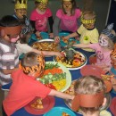 Children at table eating fruit with jungle hats on