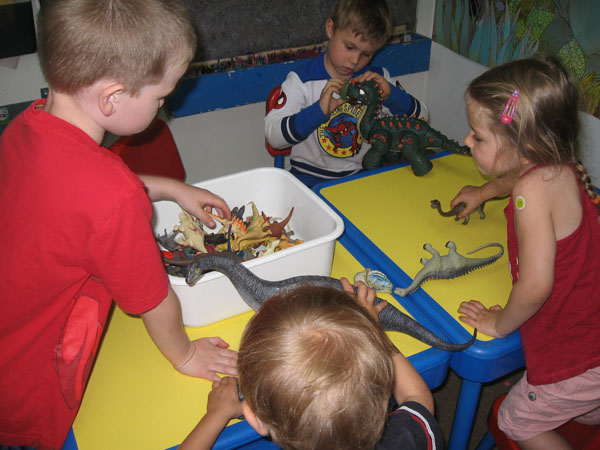 Children playing with dinosaur toys